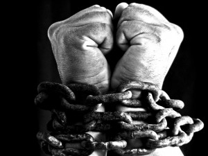 man's hands bound in chains