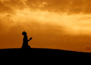 silhouette of a man kneeling in prayer