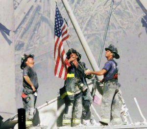 Firefighters raise a flag late in the afternoon on Tuesday, Sept. 11, 2001, in the wreckage of the World Trade Center towers in New York. In the most devastating terrorist onslaught ever waged against the United States, knife-wielding hijackers crashed two airliners into the World Trade Center on Tuesday, toppling its twin 110-story towers. (AP Photo/The Record, Thomas E. Franklin) MANDATORY CREDIT