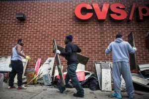 BALTIMORE, MD - APRIL 28: Volunteers help clean up debris from a CVS pharmacy that was set on fire yesterday during rioting after the funeral of Freddie Gray, on April 28, 2015, in Baltimore, Maryland. Gray, 25, was arrested for possessing a switch blade knife April 12 outside the Gilmor Houses housing project on Baltimore's west side. According to his attorney, Gray died a week later in the hospital from a severe spinal cord injury he received while in police custody. (Photo by Andrew Burton/Getty Images)